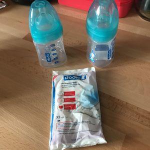 2 biberons Dodie + tétine 0/6 mois + coussinets