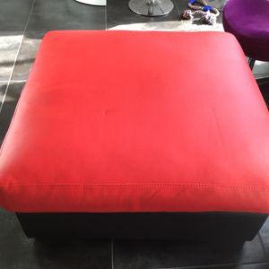 Grand pouf en cuir rouge et pieds bois foncé.